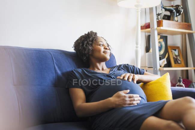 Serena donna incinta rilassante sul divano — Foto stock