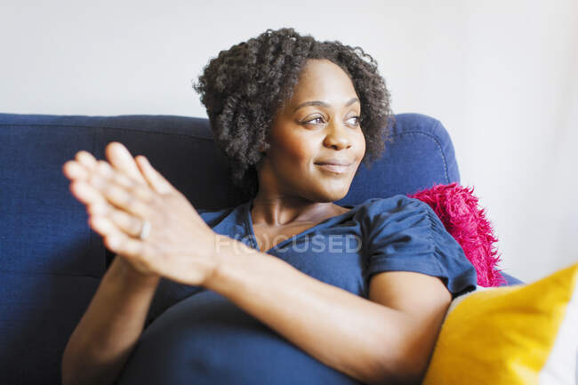 Happy pregnant woman rubbing hands together on sofa — Stock Photo