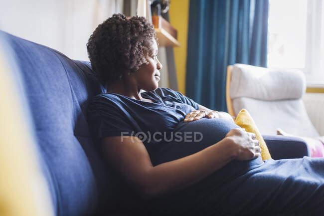Serena pensosa donna incinta rilassante sul divano — Foto stock