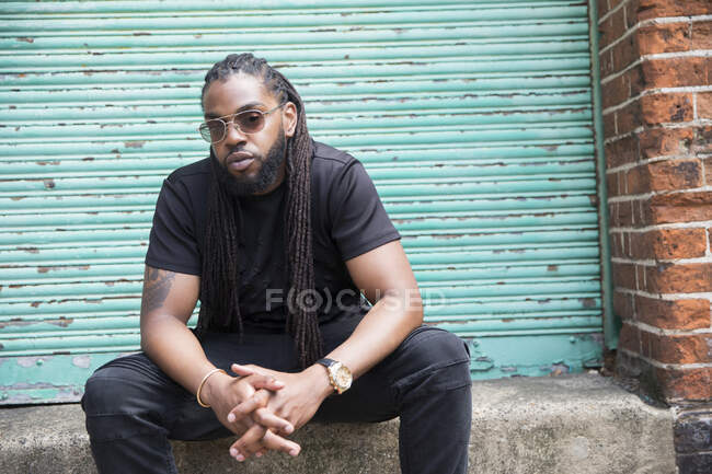 Portrait confident cool man with long braids in urban alley — Stock Photo