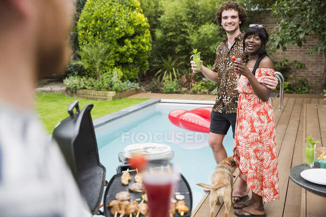 Happy young couple enjoying cocktails and barbecuing at poolside — Stock Photo