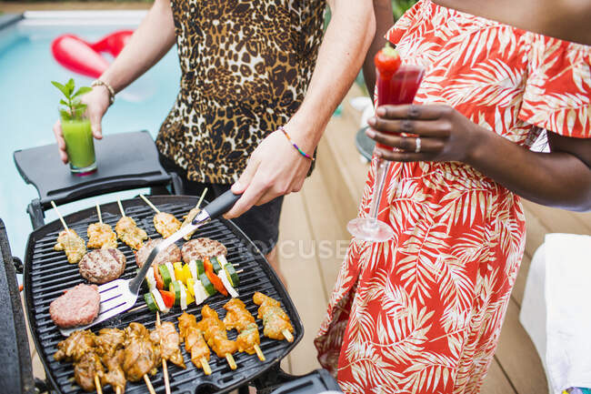 Young couple drinking cocktails and barbecuing — Stock Photo
