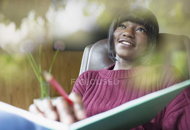 Glückliche junge Frau beim Journalismus — Stockfoto