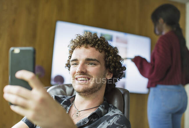 Happy young man using smart phone — Stock Photo
