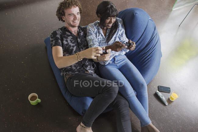 Felice giovane coppia che gioca al videogioco su sedia beanbag — Foto stock