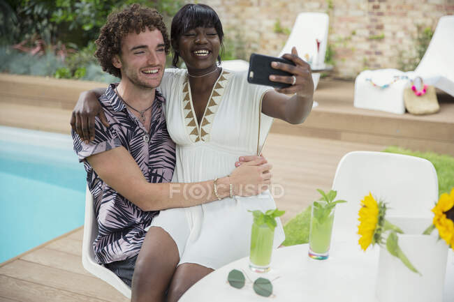 Happy young couple taking selfie with camera phone at poolside — Stock Photo