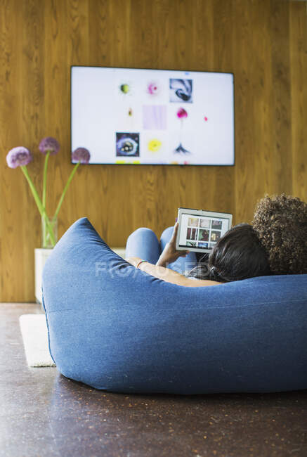 Young couple streaming photos from digital tablet to TV — Stock Photo