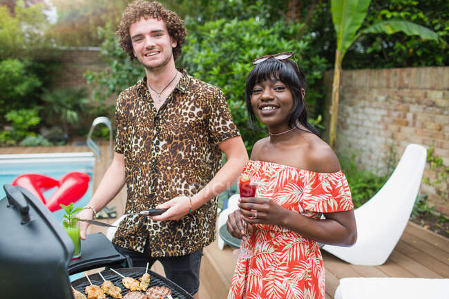 Portrait happy young couple barbecuing at poolside — Stock Photo