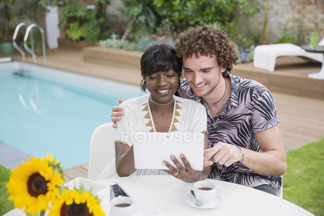 Glückliches multiethnisches Paar mit digitalem Tablet auf der Terrasse am Pool — Stockfoto