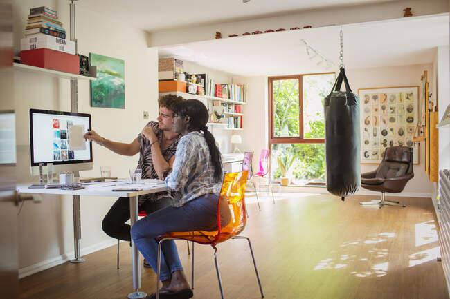 Jóvenes emprendedores creativos que trabajan en el ordenador en casa - foto de stock