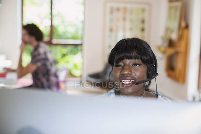 Young woman with headset working from home at computer — Stock Photo