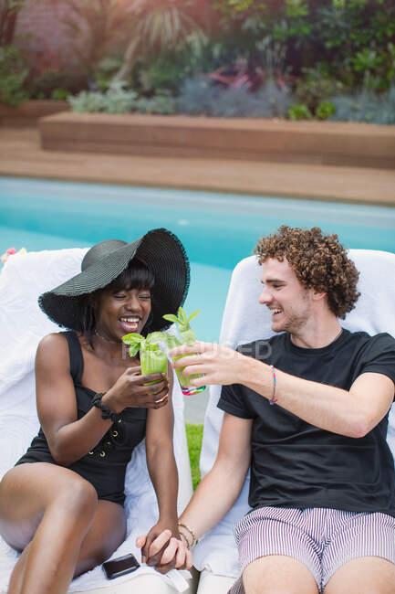 Glückliches junges multiethnisches Paar trinkt Cocktails am Pool — Stockfoto