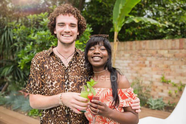 Portrait happy multiethnic couple drinking cocktails on patio — Stock Photo