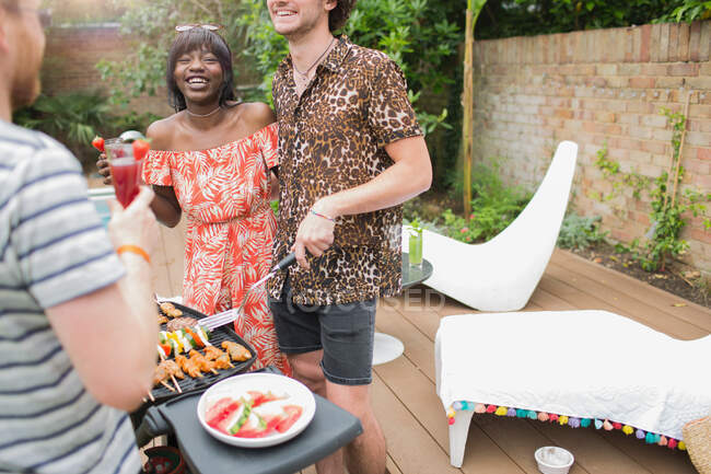 Happy young multiethnic couple barbecuing on summer patio — Stock Photo