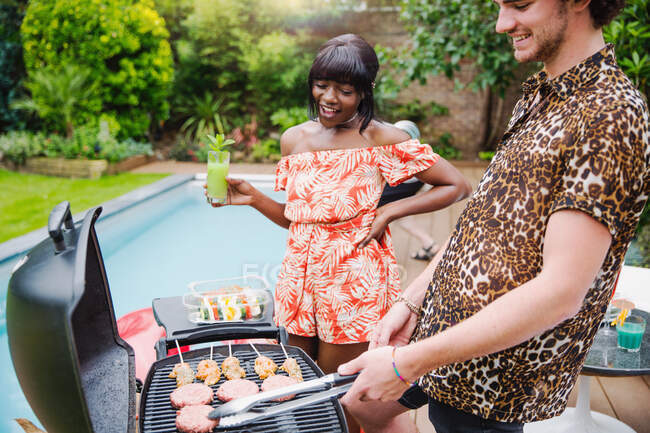 Young multiethnic couple barbecuing at poolside — Stock Photo