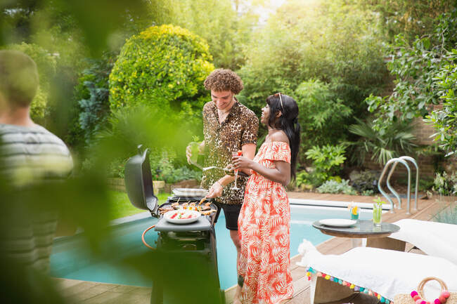 Young multiethnic couple barbecuing at summer poolside — Stock Photo