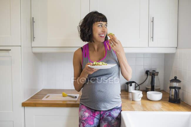 Счастливая беременная женщина ест на кухне — стоковое фото