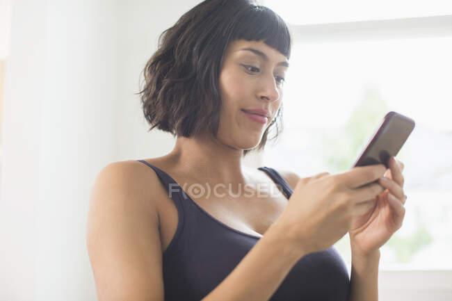Женщина в лифчике с помощью смартфона — стоковое фото