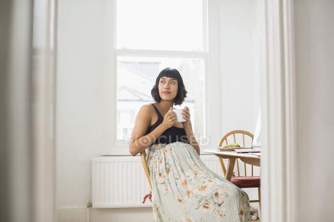Задумчивая беременная женщина пьет чай в квартире — стоковое фото