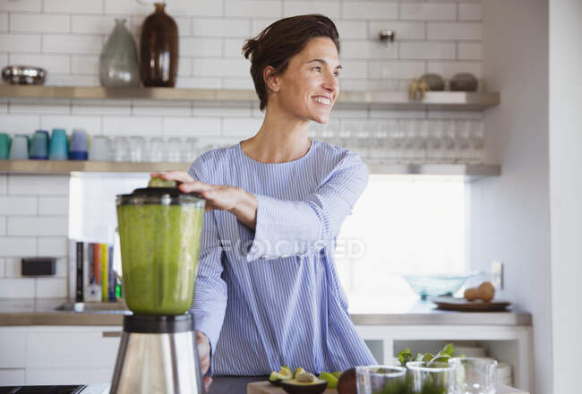 Smiling brunette woman making healthy green smoothie in blender in kitchen — Stock Photo