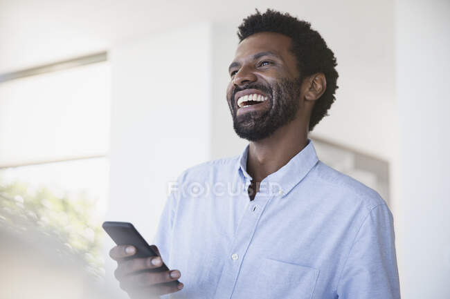Laughing man using cell phone — Stock Photo