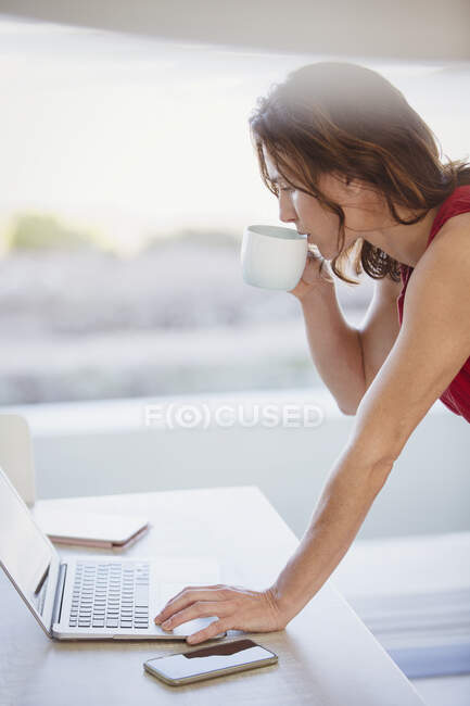 Businesswoman drinking coffee, working at laptop — Stock Photo