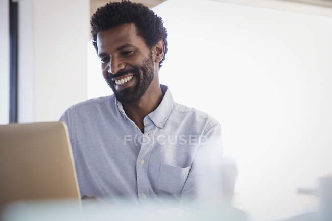 Empresário sorridente trabalhando no laptop — Fotografia de Stock