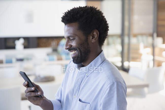 Hombre sonriente mensajes de texto con teléfono celular - foto de stock