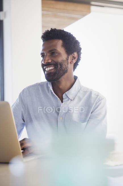 Uomo d'affari sorridente che lavora al computer portatile — Foto stock