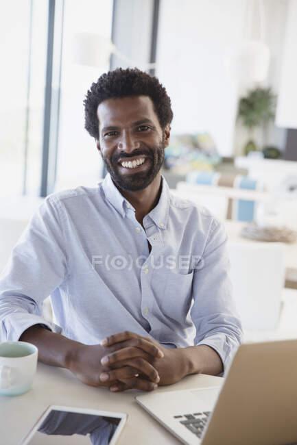 Retrato sorrindo, empresário confiante bebendo café no laptop na cozinha — Fotografia de Stock