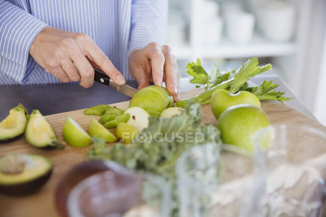 Woman cutting healthy green apples and produce on cutting board — Stock Photo