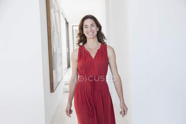 Porträt lächelnde, selbstbewusste brünette Frau, die durch den Flur geht — Stockfoto