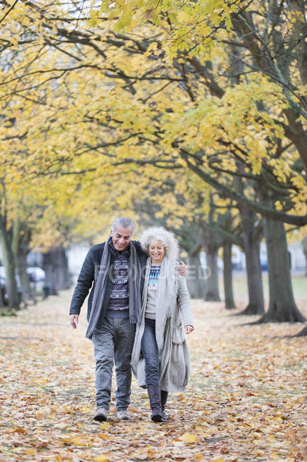 Affectionate senior couple walking among tress and leaves in autumn park — Stock Photo