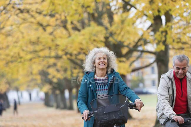 Smiling, carefree senior woman bike riding among trees in autumn park — Stock Photo