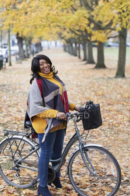 Портрет усміхається, впевнена жінка їде на велосипеді між деревами й листям осіннього парку. — стокове фото
