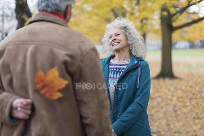 Verspielter Senior-Ehemann überrascht Ehefrau mit Herbstblatt im Park — Stockfoto
