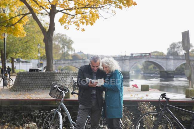 Старша пара з велосипедами подорожує, дивлячись на путівник уздовж осінньої річки. — стокове фото