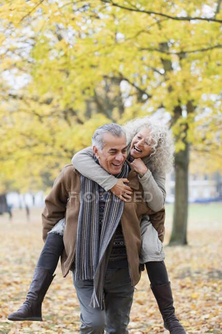 Playful senior couple piggybacking in autumn park — Stock Photo