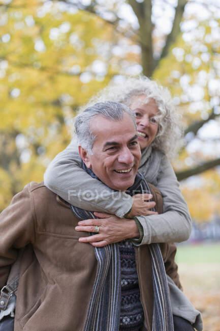 Playful, smiling senior couple piggybacking in autumn park — Stock Photo