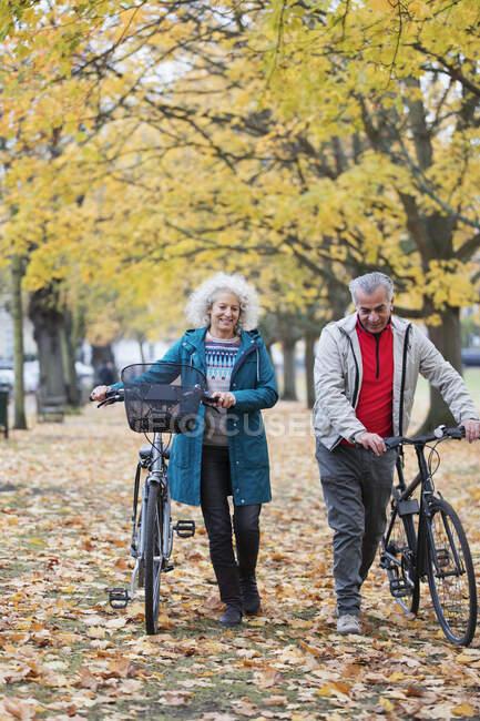 Couple aîné à vélo de marche entre les arbres et les feuilles dans le parc d'automne — Photo de stock