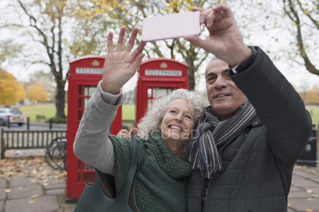 Smiling senior couple taking selfie in autumn park in front of red telephone booths — Stock Photo
