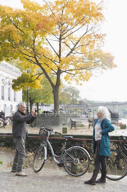 Старший мужчина фотографирует жену с велосипедом в осеннем городе — стоковое фото