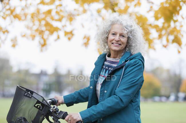 Portrait confident, smiling senior woman bike riding in autumn park — Stock Photo