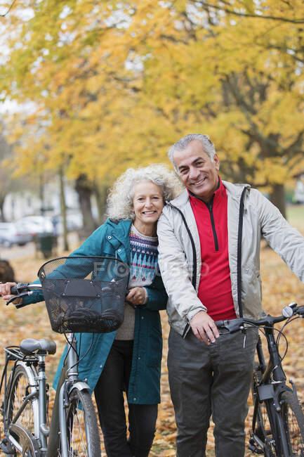 Porträt lächelndes, unbeschwertes Seniorenpaar mit Fahrrädern im Herbstpark — Stockfoto