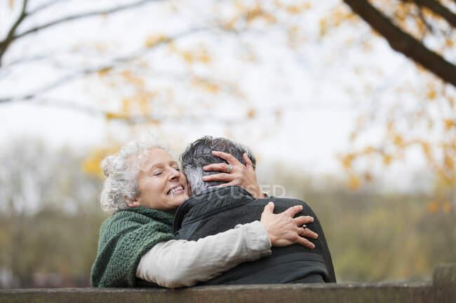 Zärtliches Senioren-Paar umarmt sich im Herbstpark — Stockfoto