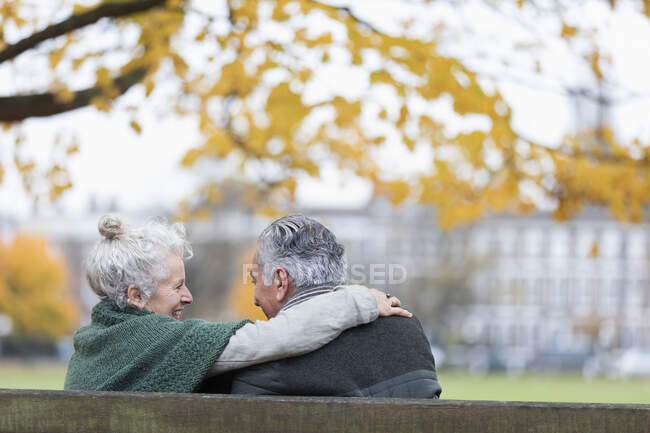 Carefree, affectionate senior couple hugging on bench in autumn park — Stock Photo