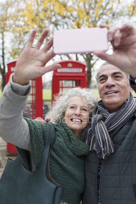 Smiling senior couple taking selfie in park in front of red telephone booths — Stock Photo