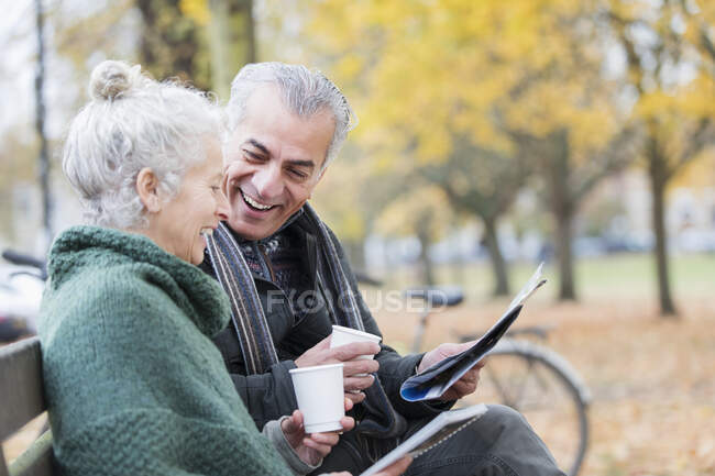 Lächelndes Seniorenpaar liest Zeitung und trinkt Kaffee auf Bank im Herbstpark — Stockfoto