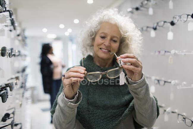 Senior woman shopping for eyeglasses in optometry shop — Stock Photo
