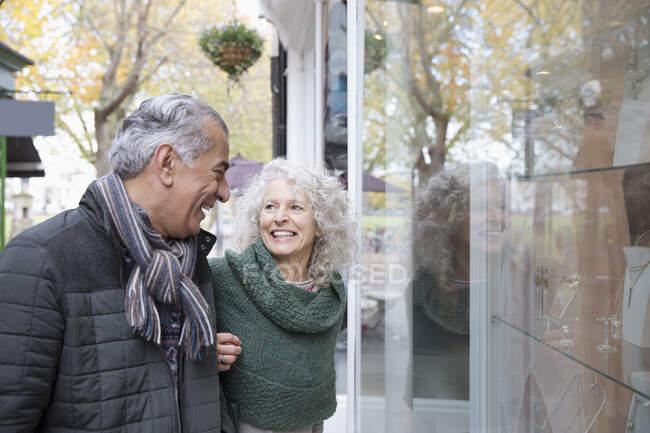 Senior couple window shopping at storefront — Stock Photo